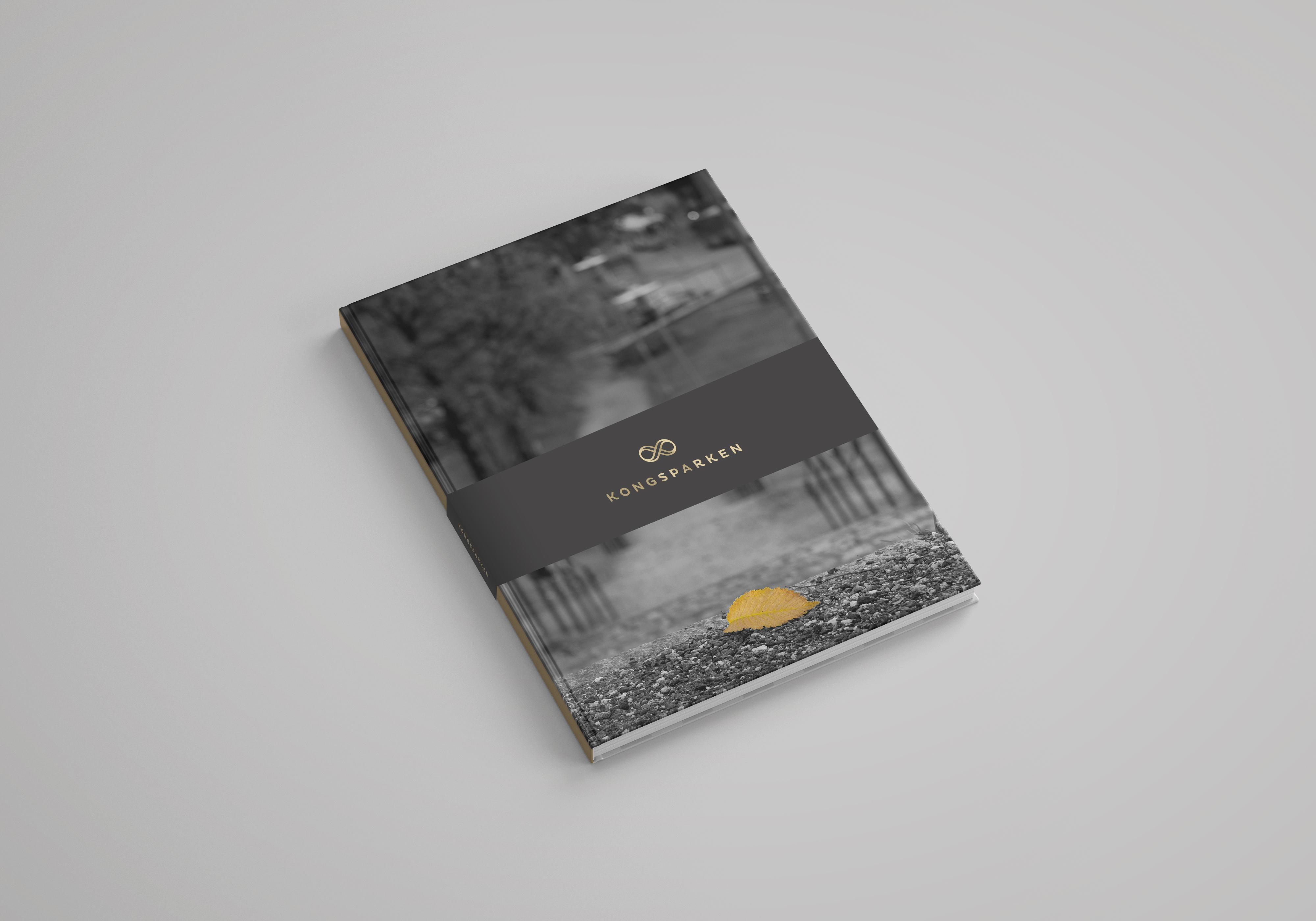 Mockup av Kongsparken-prospektet i gull og grå