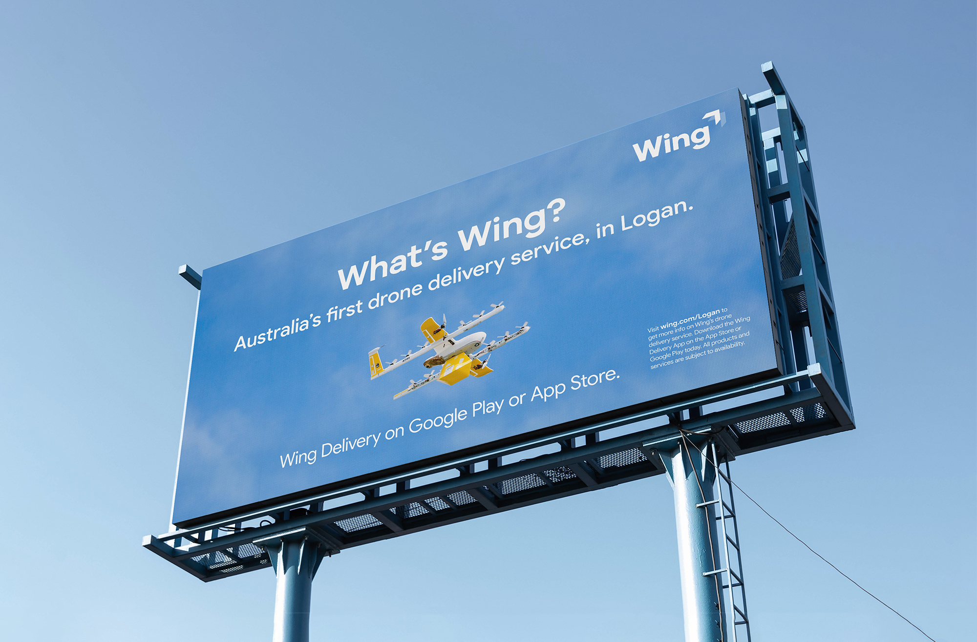 """Image of a billboard featuring photography of a Wing commercial drone. The billboard says """"What's Wing? Australia's first drone service, in Logan. Wing Delivery on Google Play or App Store."""""""