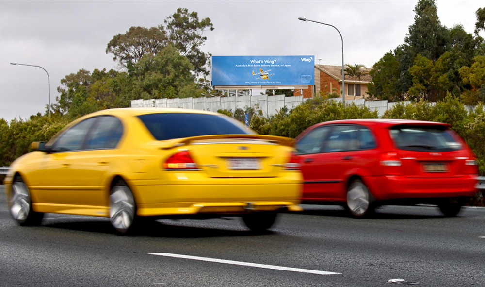 """Image of a billboard on-site above a busy highway. The billboard featuring photography of a Wing commercial drone. The billboard says """"What's Wing? Australia's first drone service, in Logan. Wing Delivery on Google Play or App Store."""""""