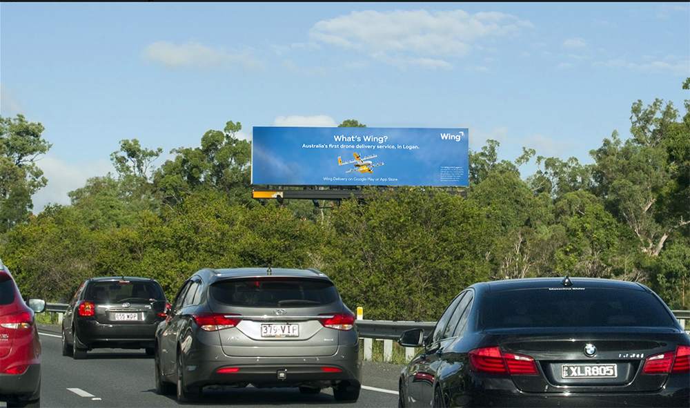 """Image of a billboard on-site at a secondary location above a highway. The billboard featuring photography of a Wing commercial drone. The billboard says """"What's Wing? Australia's first drone service, in Logan. Wing Delivery on Google Play or App Store."""""""