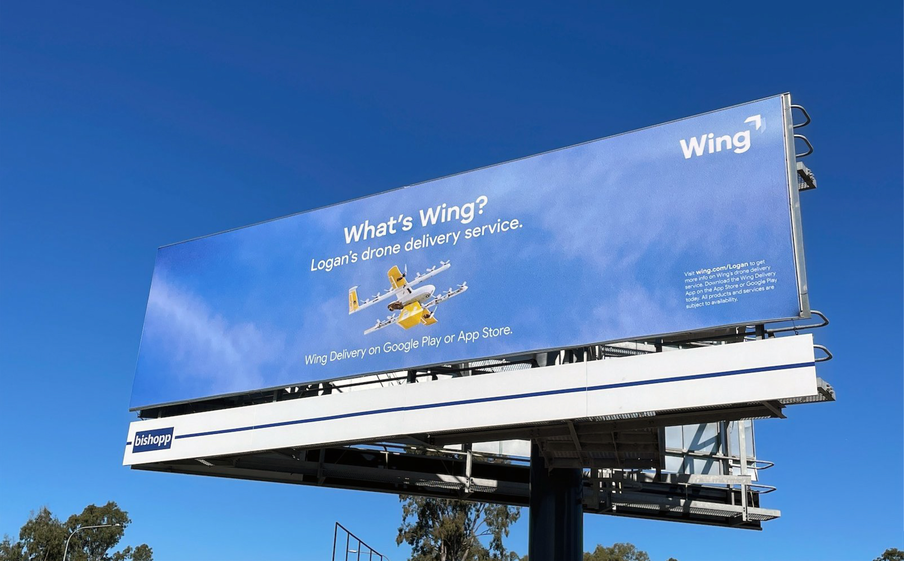 """Image of a billboard on-site at a secondary location in a clear, blue sky among trees. The billboard featuring photography of a Wing commercial drone. The billboard says """"What's Wing? Australia's first drone service, in Logan. Wing Delivery on Google Play or App Store."""""""