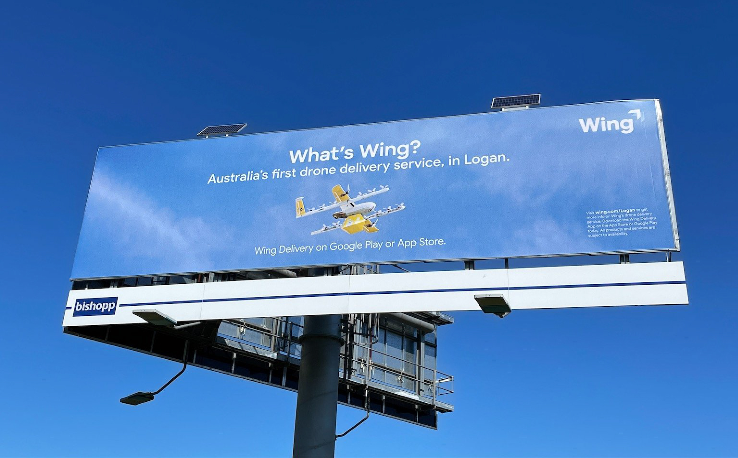 """Image of a billboard on-site in a clear blue sky. The billboard featuring photography of a Wing commercial drone. The billboard says """"What's Wing? Australia's first drone service, in Logan. Wing Delivery on Google Play or App Store."""""""