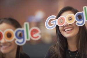 Foto Case Estapar, duas moças sorrindo com um óculos com o formato do logo do Google no rosto
