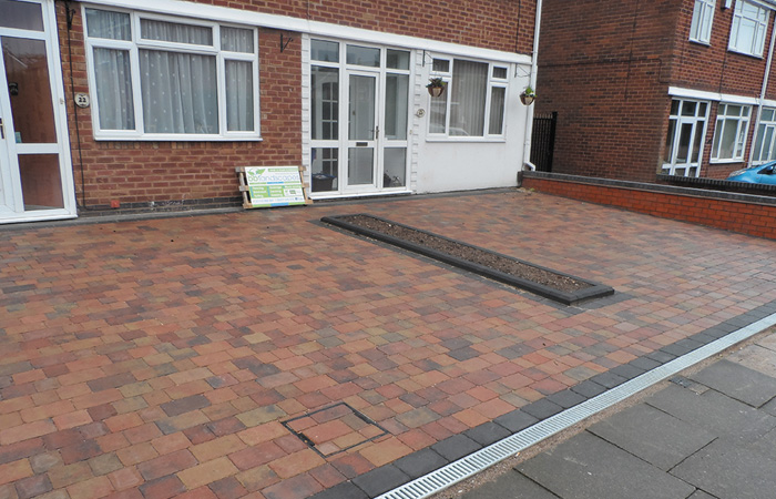 Orchid flame Rumbled paving set double driveway with single border in charcoal, middle diving planter, ACO channel drainage system and boundary wall installed.