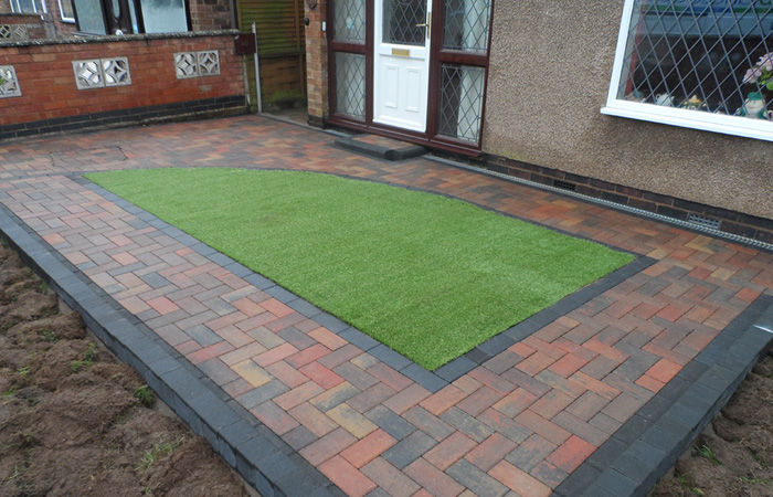 Autumn mix standard paving set driveway with a single border in charcoal, K.L kerb set planters, inset manhole tray, ACO channel drainage system, K.S kerb step and artificial lawn area.