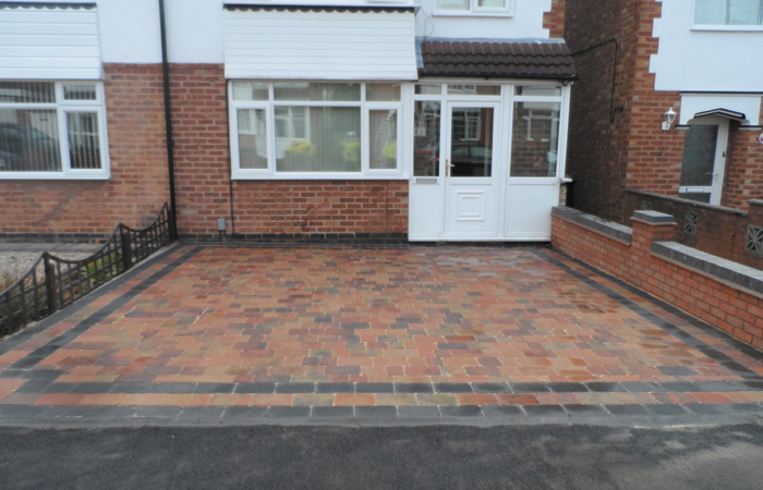 Orchid flame Rumbled paving set driveway with triple borders using charcoal, boundary wall installed and an ACO channel drainage system.