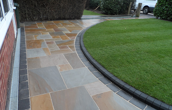 Camel Indian natural stone with rumbled charcoal borders, K.S kerb sets, ACO channel drainage system and new lawn using Rolawn medallion turf.