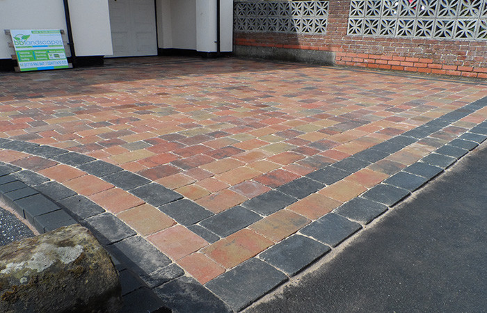 Orchid flame Rumbled set driveway with a triple border in charcoal, ACO channel drainage system and inset rodding eye tray paved in.