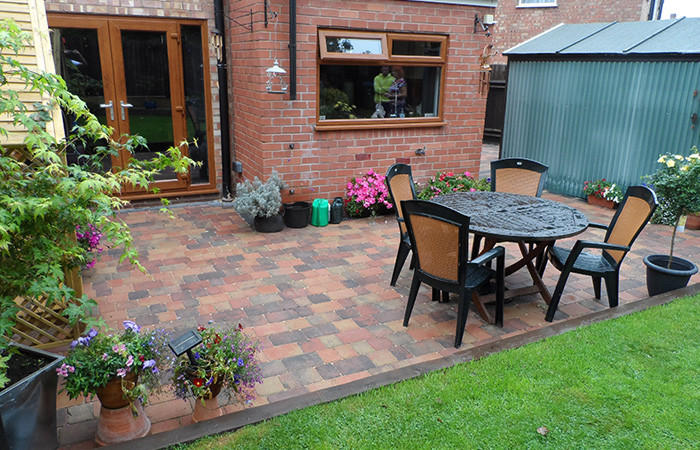 Orchid flame Rumbled paving set double driveway and patio with charcoal borders, K.L kerb set steps and planter retainers.
