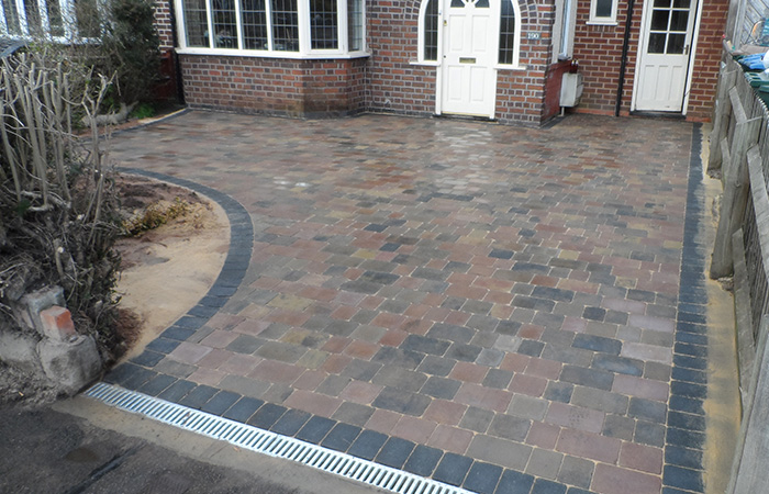 Bracken Rumbled paving set driveway with a single charcoal border, radius planter areas and an ACO channel drainage system.