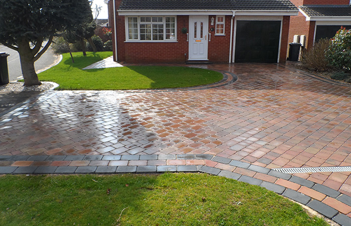Autumn mix Rumbled paving set driveway with a triple border in charcoal, ACO channel drainage system and new lawn areas using Rolawn medallion turf.
