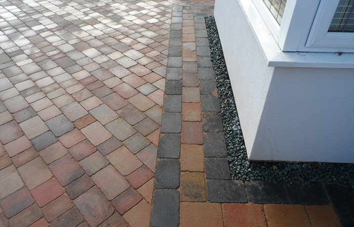 Orchid flame Rumbled paving set large driveway with a triple border using Charcoal, K.S kerb set lawn retainer, and an inset manhole tray paved in.