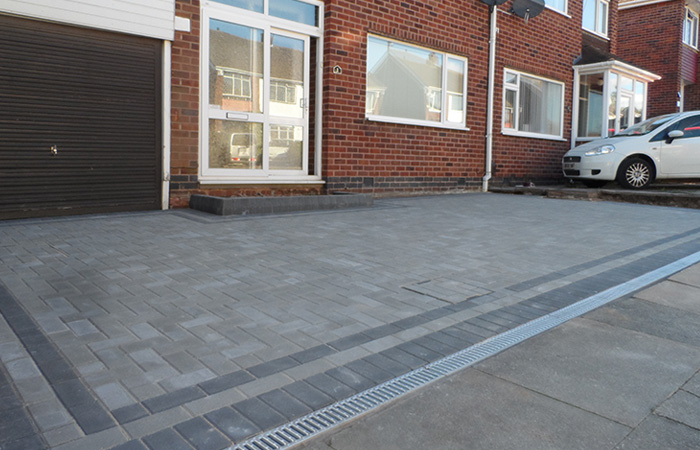 Natural standard paving set driveway with a triple border in charcoal, K.L kerb set step, inset manhole tray and an ACO channel drainage system.