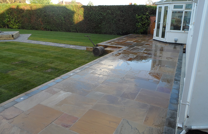 Mixed size camal natural stone patio with large charcoal rumbled block, sleeper retaining beds and new lawn.