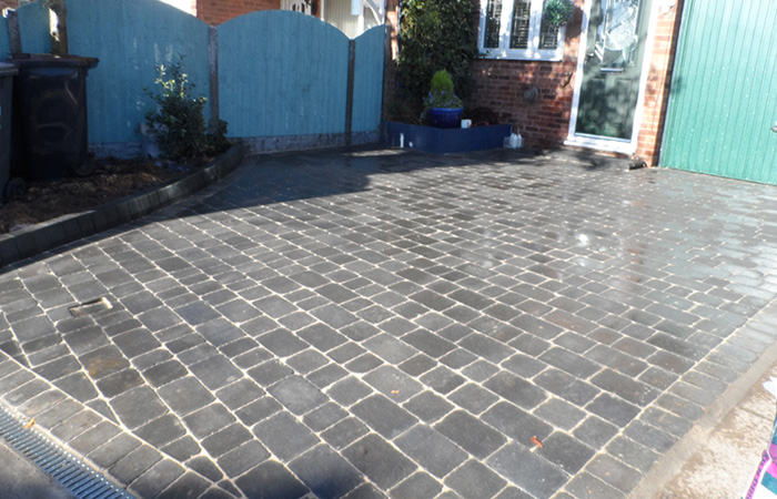 Charcoal Rumbled paving set driveway with K.L kerb planter and an ACO channel drainage system.