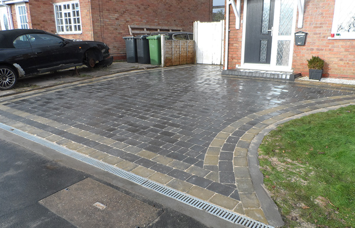 Charcoal Rumbled paving set driveway with triple border in burnt willow, K.L kerb step and ACO channel drainage system.