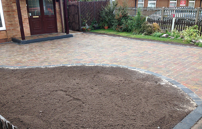 Autumn mix Rumbled paving set driveway with single charcoal border, K.L kerb platform step and large planter area.