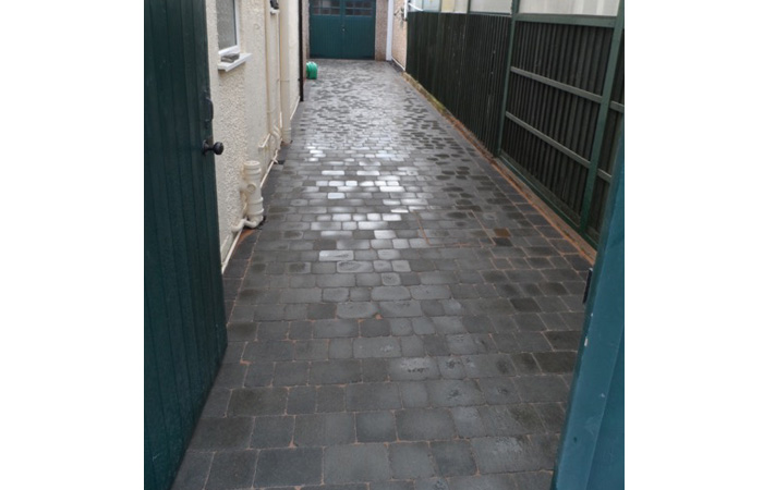 Ash Rumbled paving set driveway with single charcoal border and ACO channel drainage system.