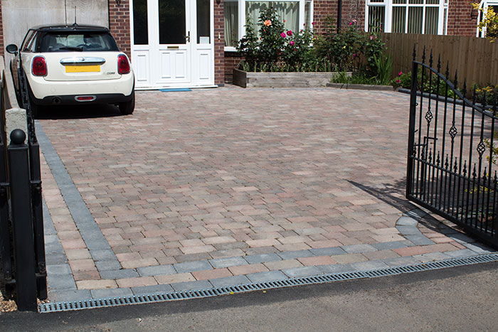 Autumn mix Rumbled paving set driveway with timber planter and ACO channel drainage system.