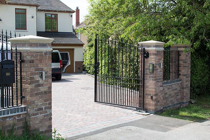 Brindle Rumbled paving set driveway with rustic brick wall and pillars.