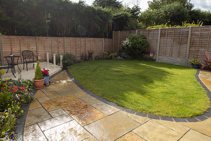 Mixed size yellow limestone patio with large charcoal rumbled block.