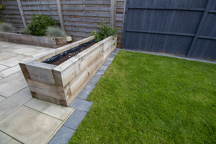 Mixed size Raj natural stone patio with a large charcoal rumbled block and a new lawn.
