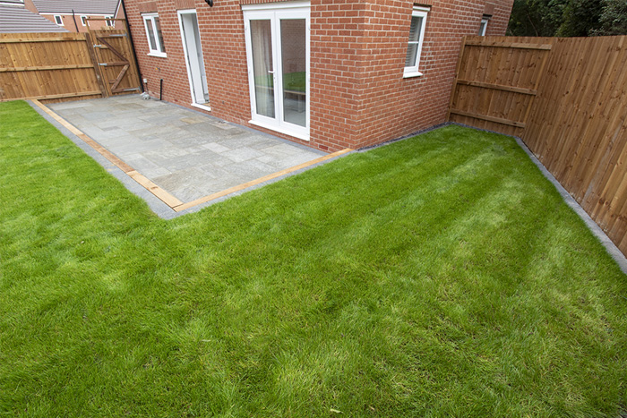 Mixed size grey sandstone with a large charcoal rumbled block, sleeper step and new lawn.