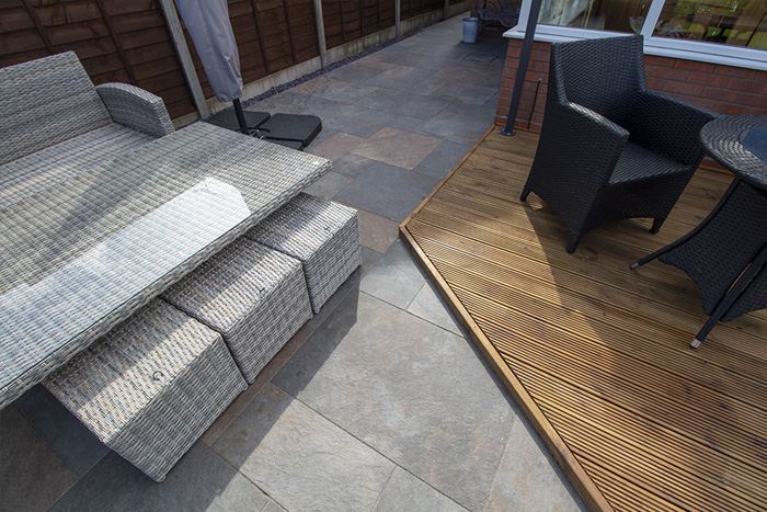 Mixed sized rustic porcelain patio, raised treated decking area and a new lawn and finished with blue slate.
