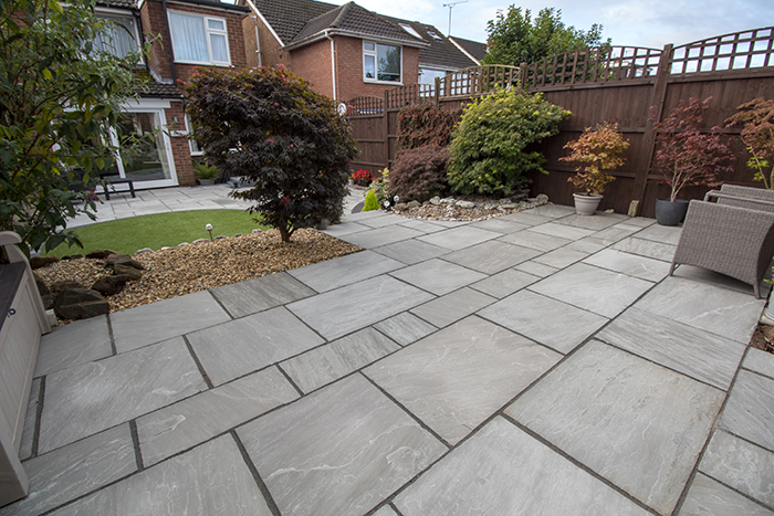 Mixed size grey sandstone patio with a large charcoal rumbled block border, artificial grass also edged with charcoal blocks.