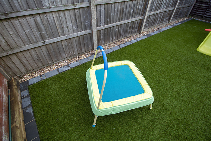 Artificial grass with large charcoal rumbled block border.