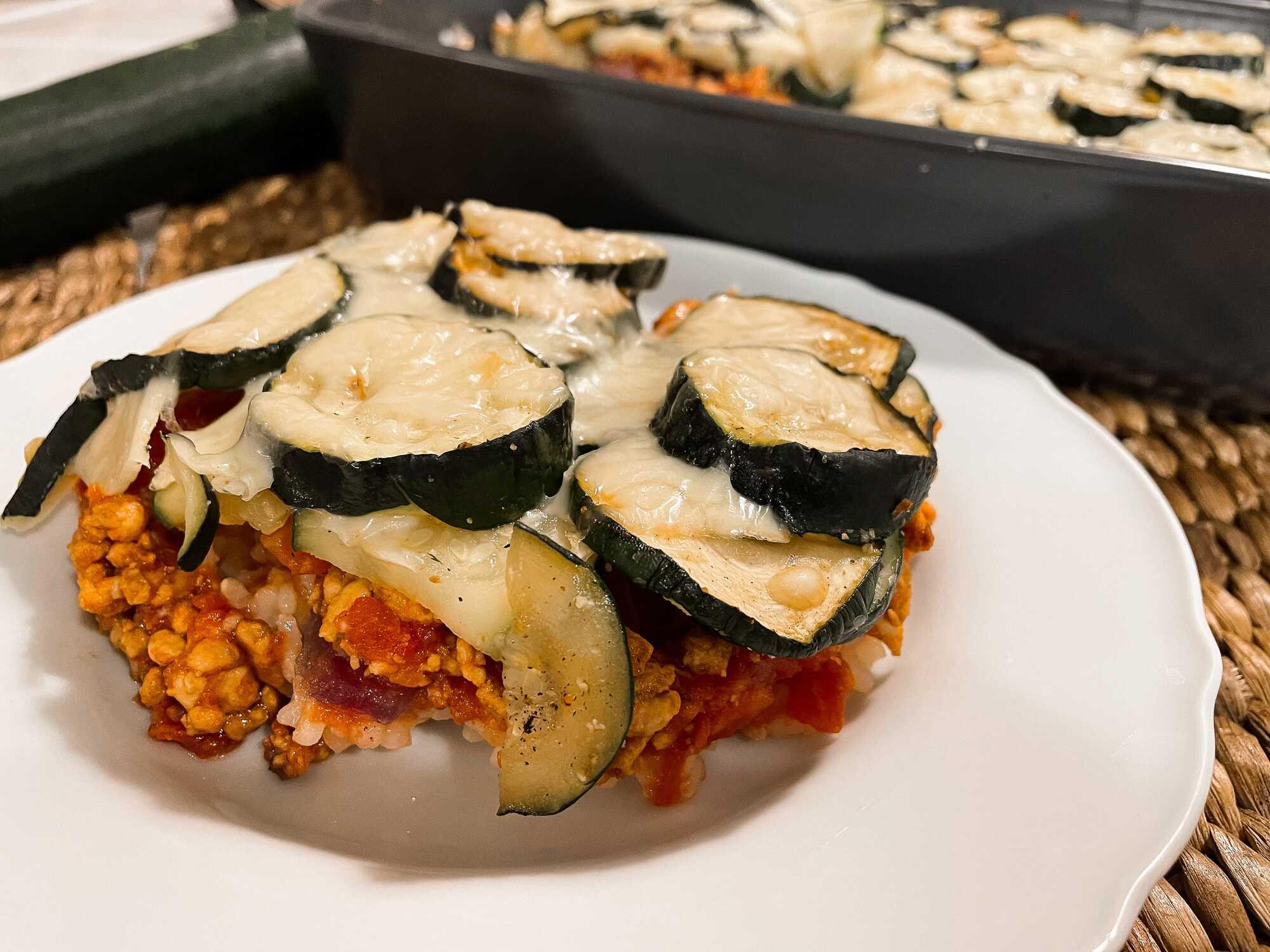 Sur son lit de riz couleur rouge grâce aux tomates, le hachis de viande viens par dessus et enfin les courgettes coupées en grosses tranches.