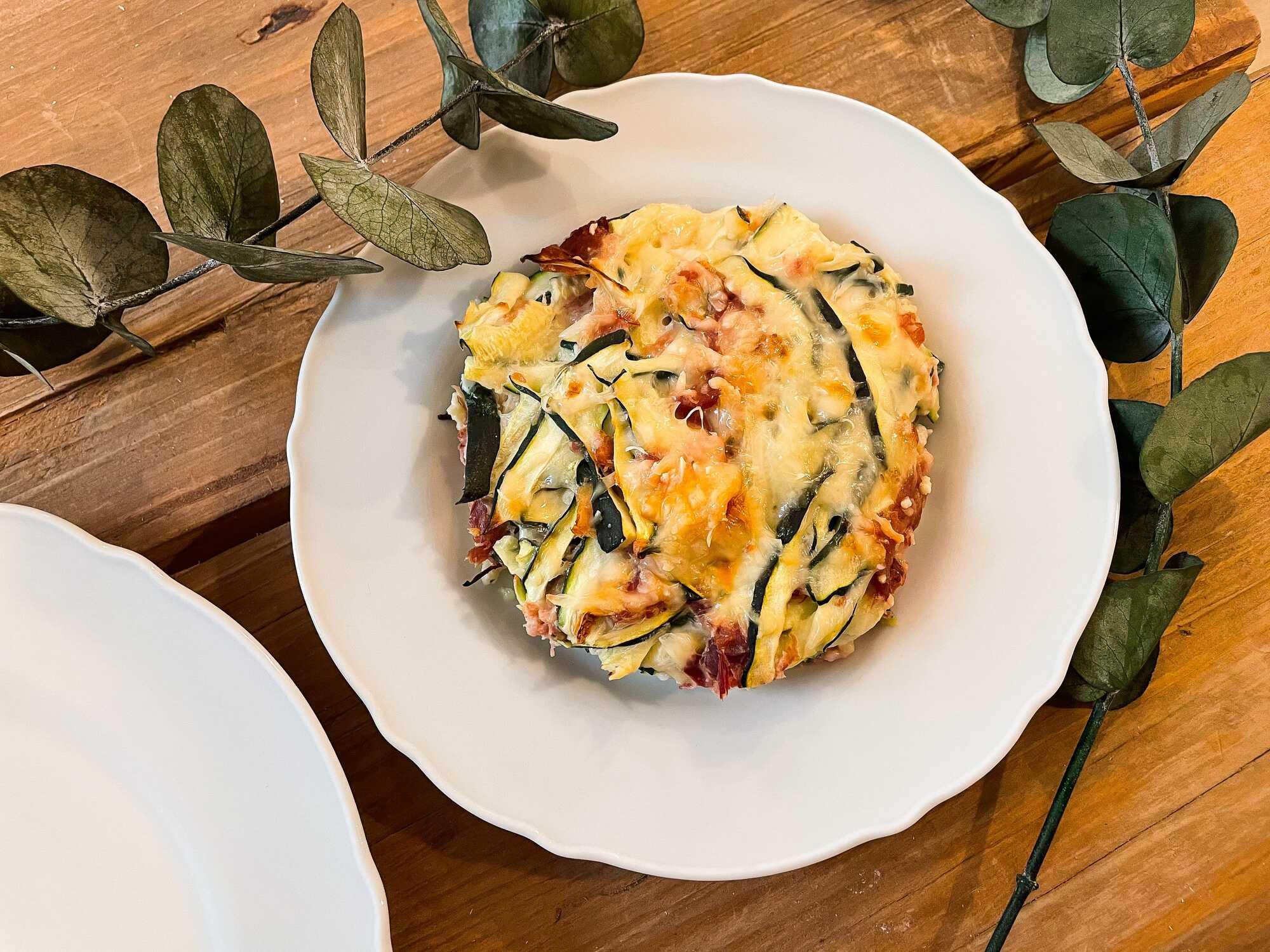 Présenté dans un plat creux blanc, les courgettes, le jambon ainsi que le fromage sont du plus bel effet.