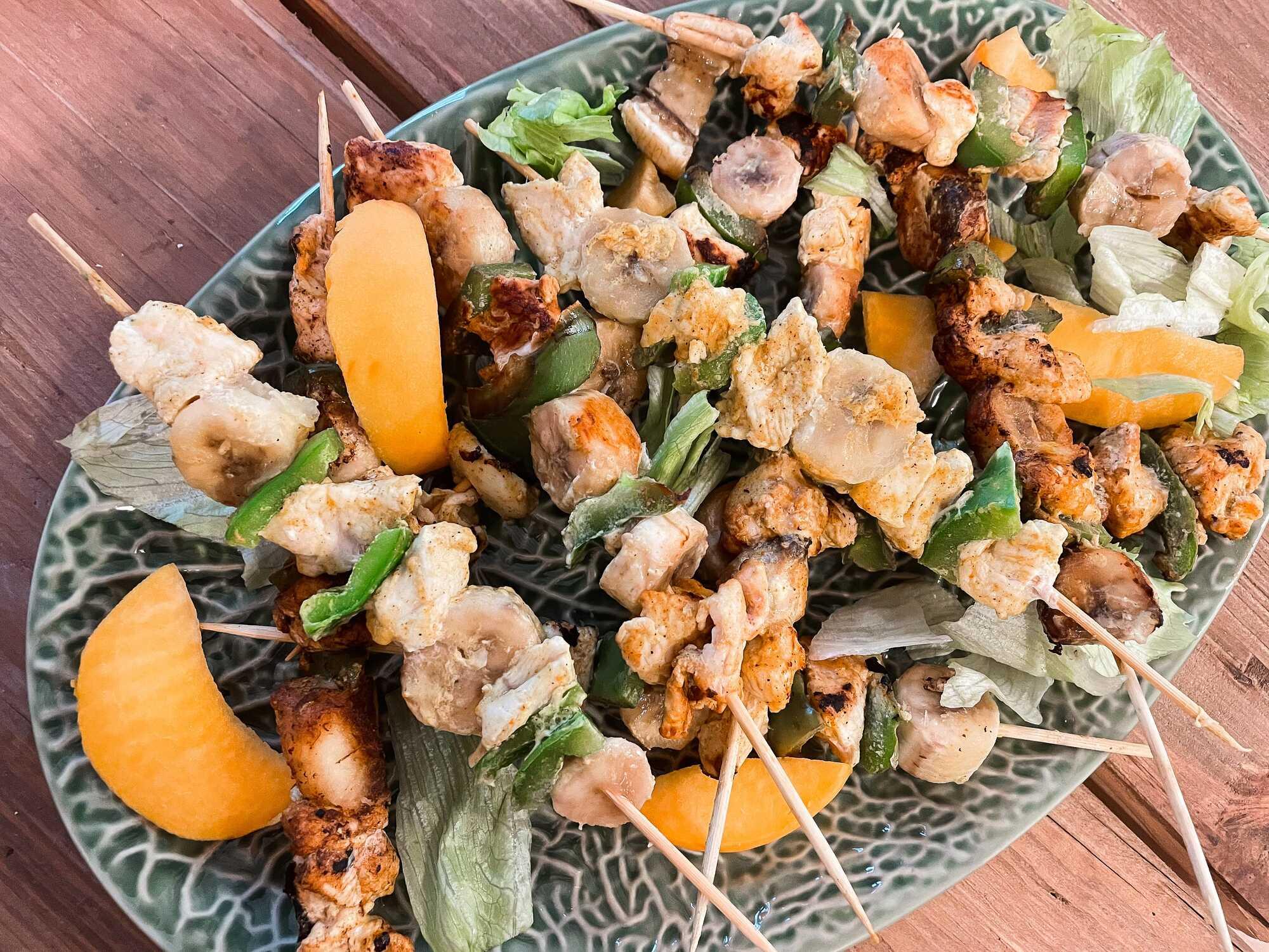 Sur un plat ovale sont disposées les brochettes. Quelques tranches de mangue décorent cette recette. Effet visuel garantie !