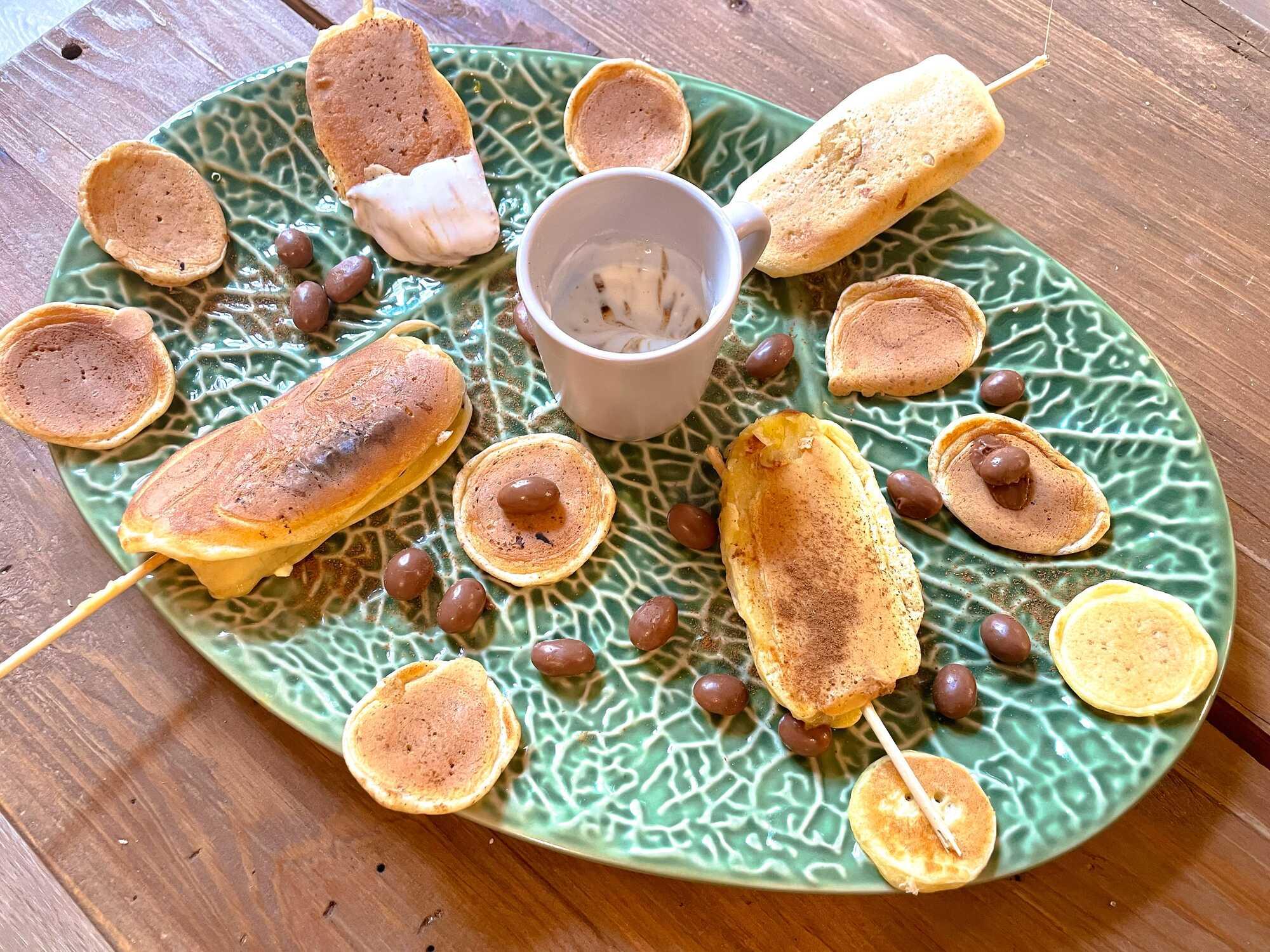 Sucettes de pancake/banane déposés sur un joli plat ovale vert, décoré de pépites de chocolat.