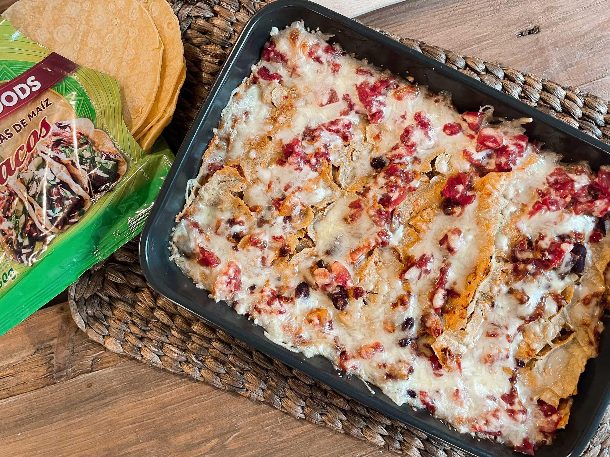 Enchilades végétariennes au fromage, haricots rouges, & protéines de soja présentées dans un plat à gratin.