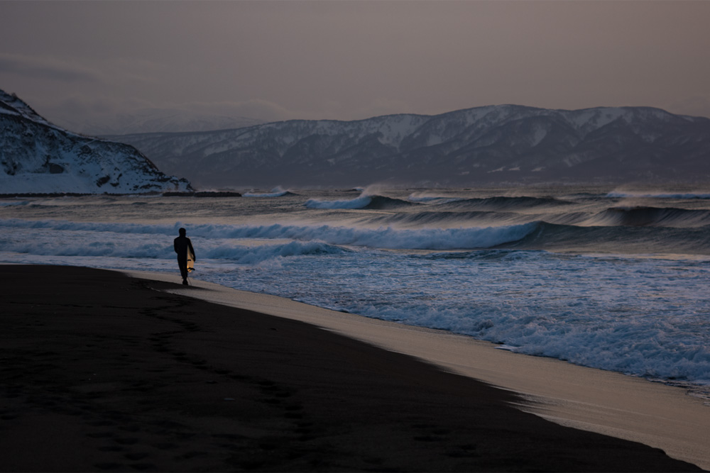 Man walking along Hokkaido beach with surfboard