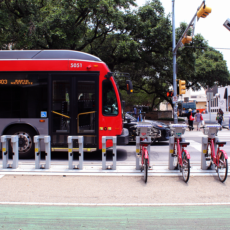 A picture of a bus waiting at a stop light next to a rack of b-cycle bicycles