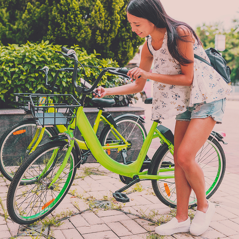 a picture of a woman using her phone to unlock a green bikeshare bicycle