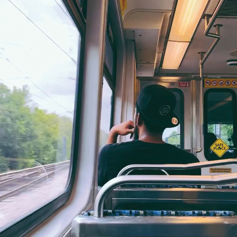 a picture of a man wearing a backwards cap sitting on a dart train looking out the window