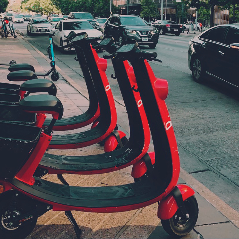 a picture of parked ojo scooters next to traffic