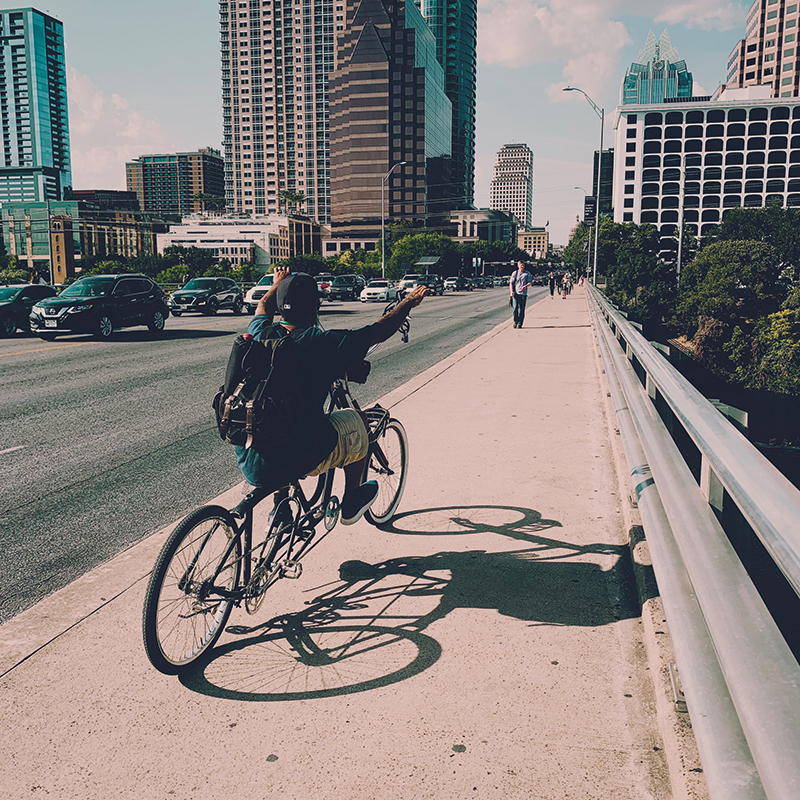 a picture of a man riding a custom bicycle down a side walk that is on a bridge