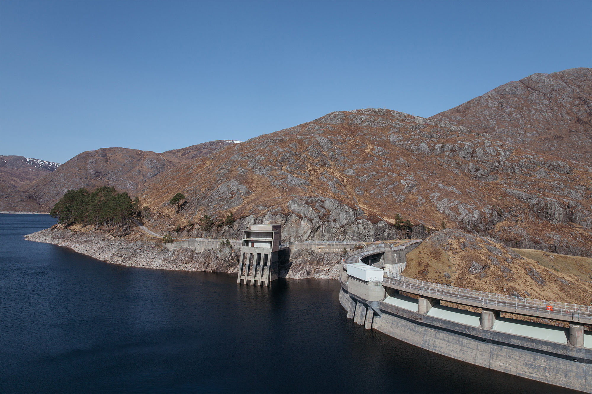 The curved Monar Dam holding back deep blue water.