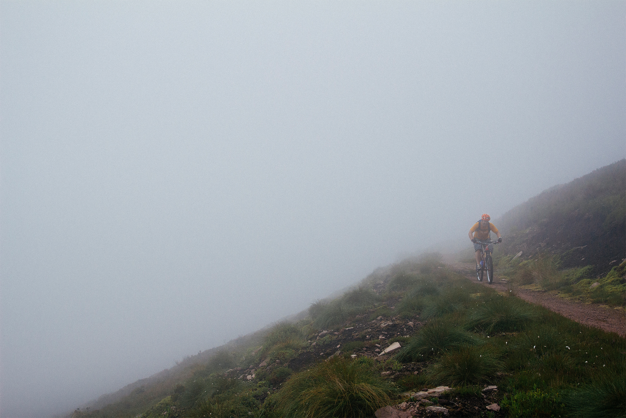 A mountain biker appears through the fog, high up on the edge of a hillside.
