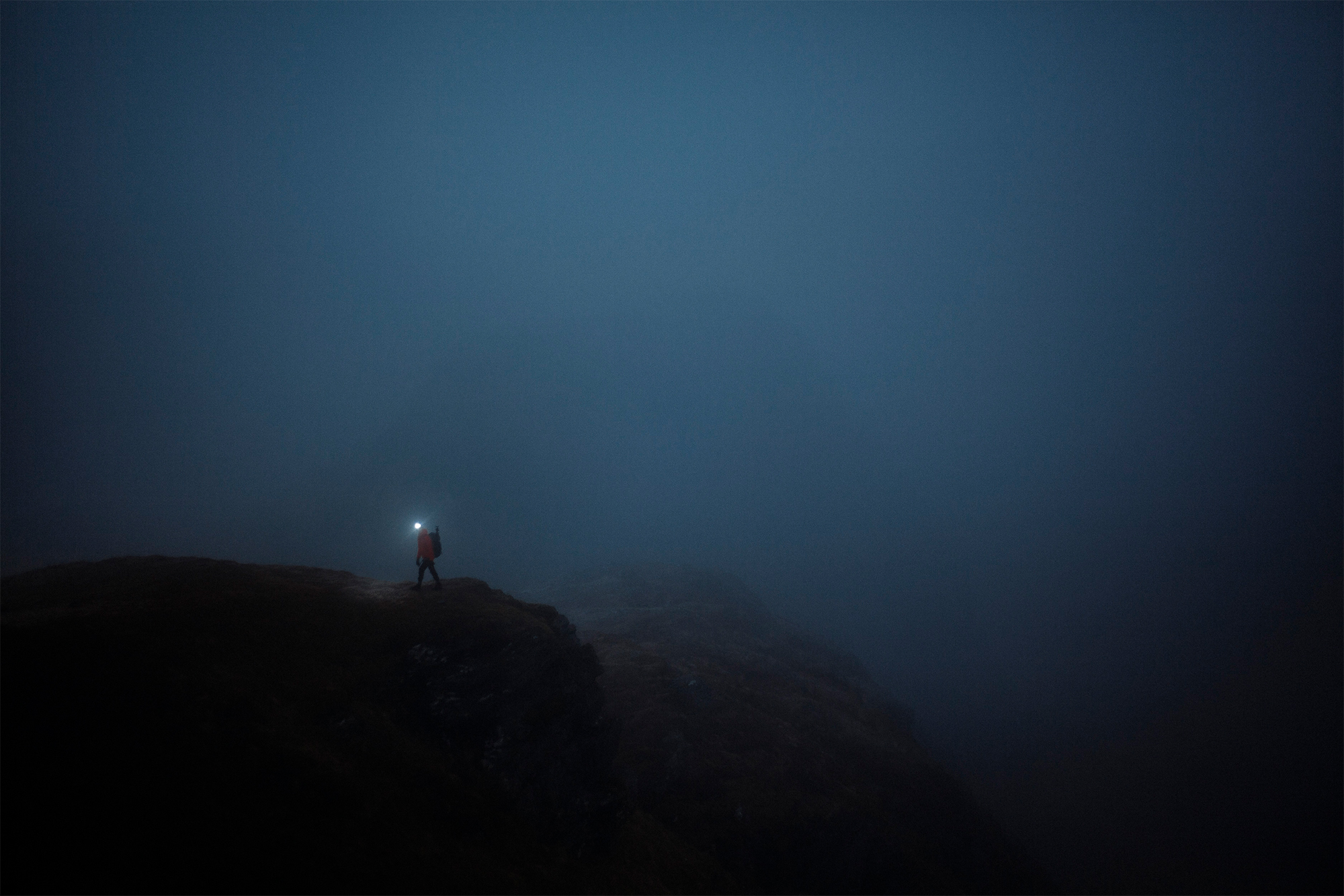 The head torch of a mountain walker tracks along a ridgeline in the darkness.