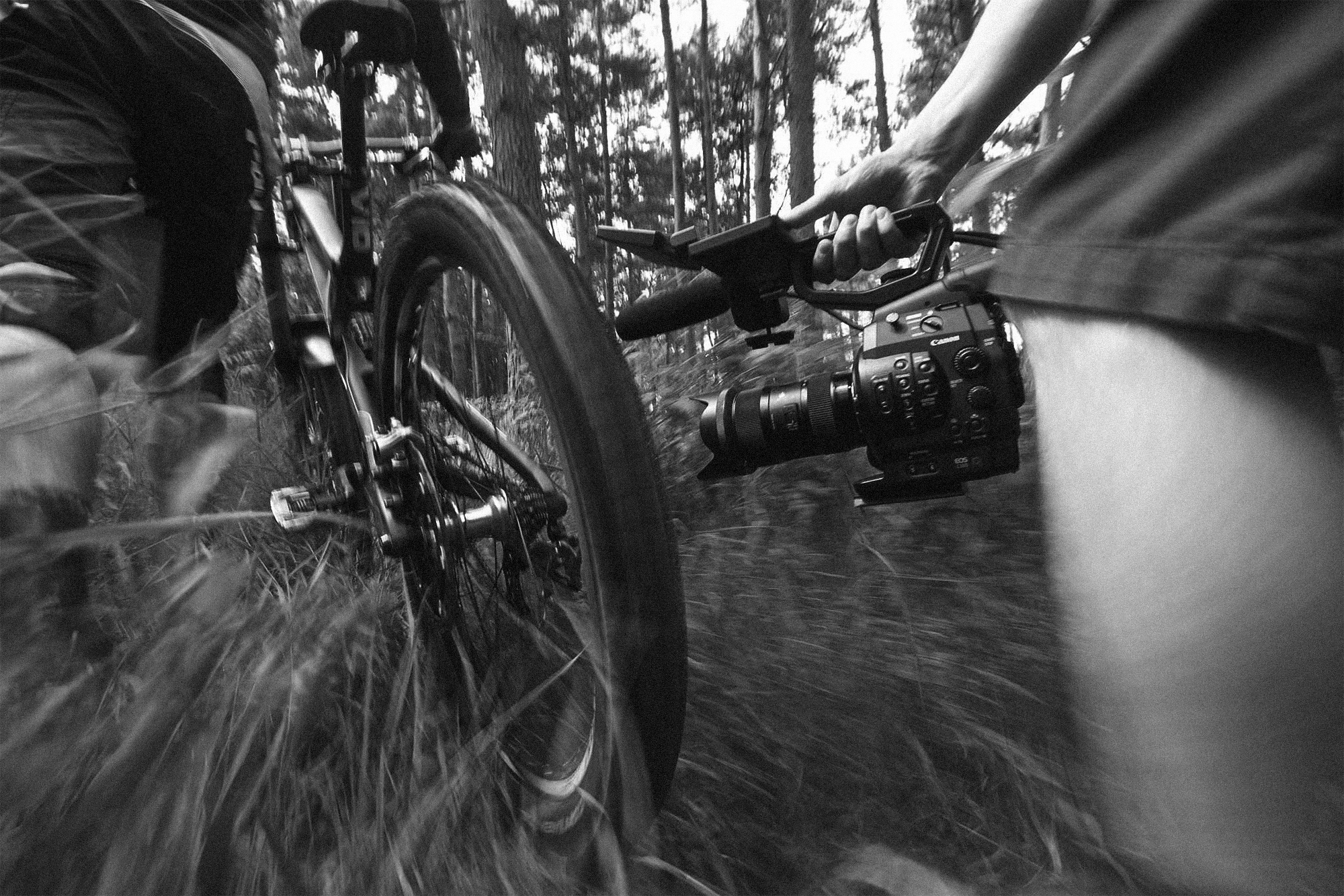 A mountain bike being pushed along a grassy track, with filmmaker and camera tracking alongside.