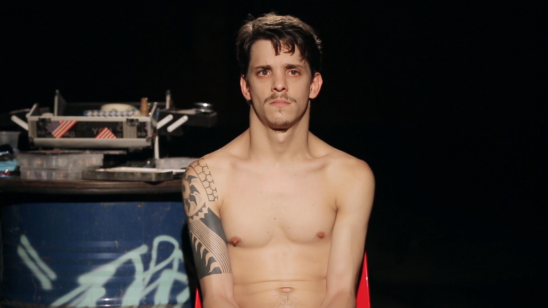 Bild på Daniel med bar överkropp. Han har en tatuering på höger arm och sitter på en röd stol.
