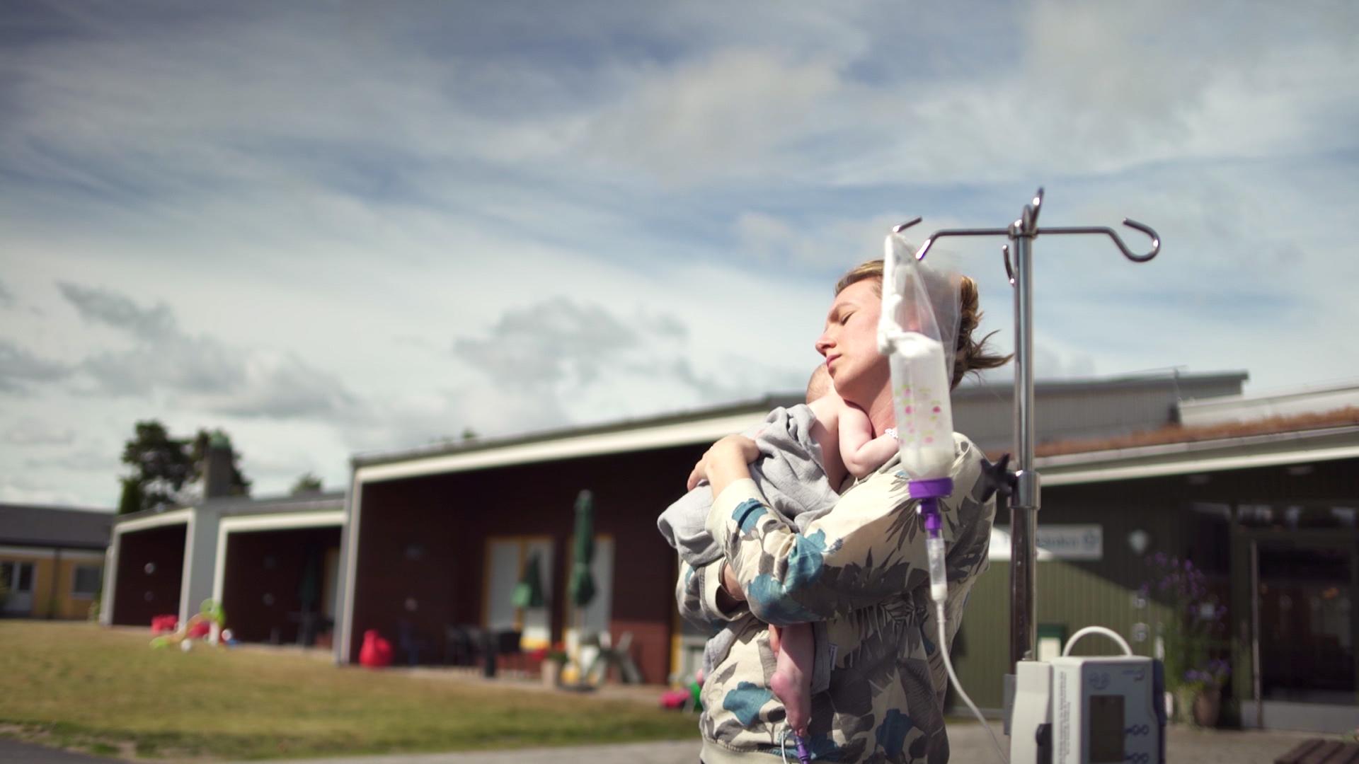 Mamma Maja håller bebisen Roj i famnen framför ett hus. I förgrunden syns Rojs droppställning.