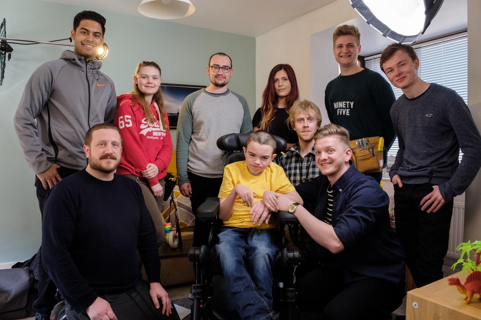 Gruppbild på filmens medverkande. Huvudpersonen sitter i mitten med gul tröja.