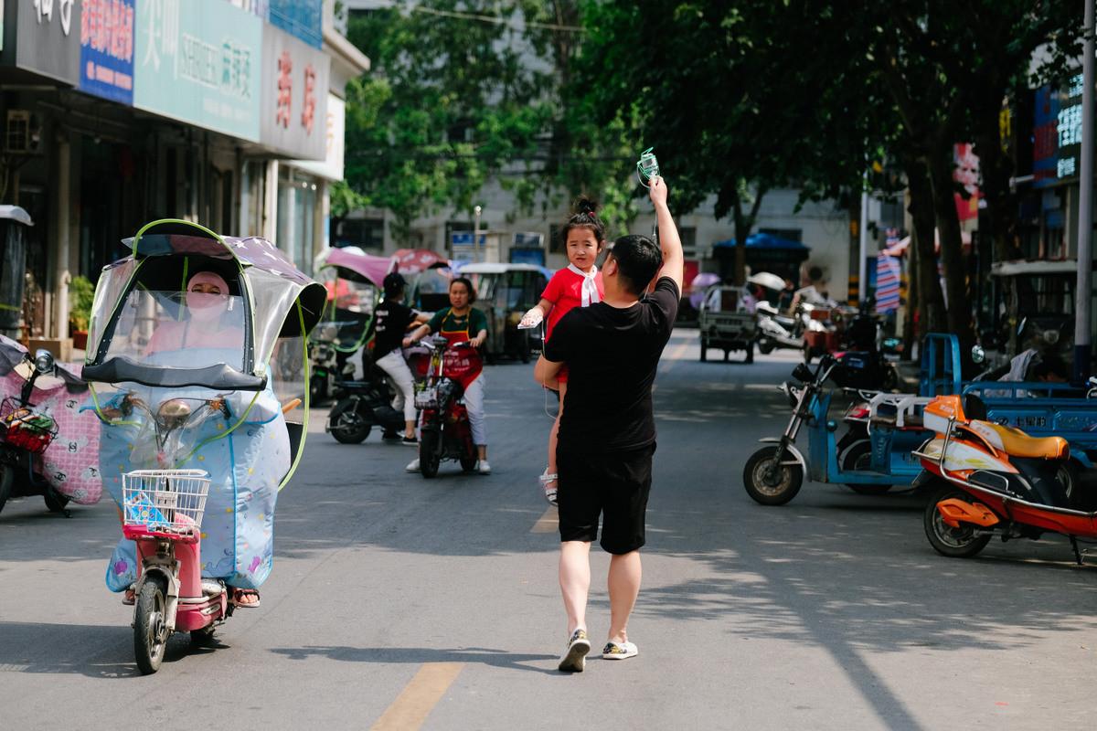 En stillbild från A Race Against Time. En man går på en gata med ett barn i famnen. De går bortåt. Omkring dem syns olika sorters mopeder.
