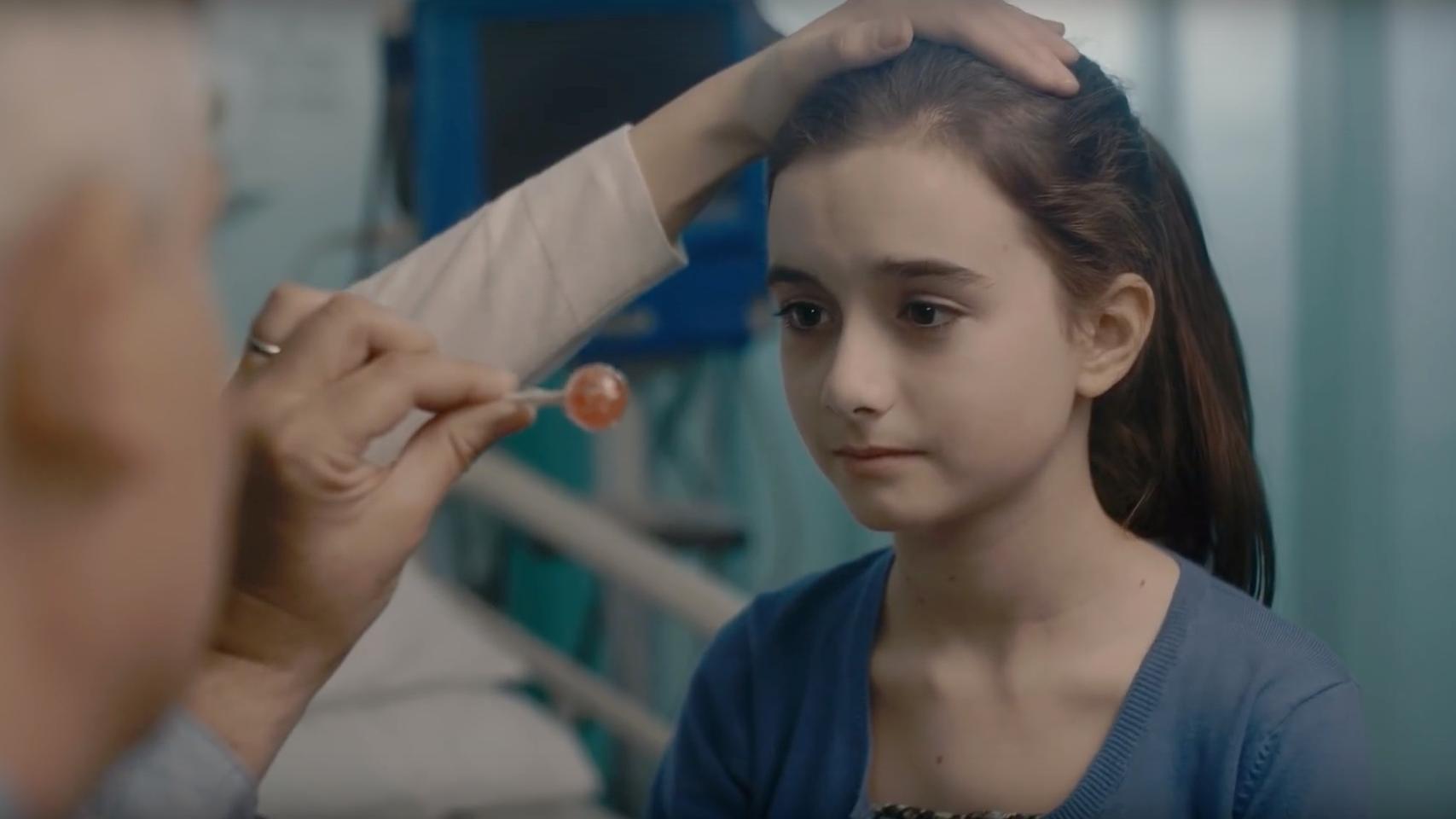 Stillbild från filmen. Millie ser bekymrad ut under en undersökning. En läkare håller en hand på hennes huvud och en annan person håller ett klubbliknande föremål framför henne.